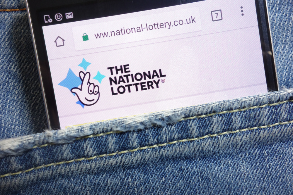 mobile phone inside denim pocket displaying the uk national lottery website