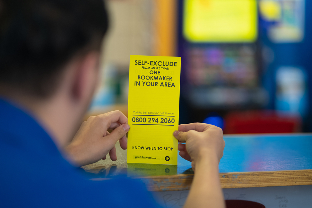 man-holding-gamble-aware-self-exclusion-leaflet