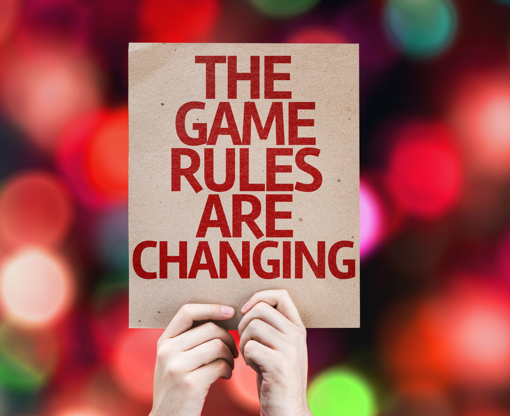 hands holding up a poster that reads the game rules are changing