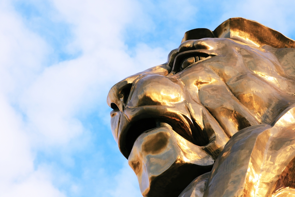 close-up of a golden lion statue against a blue sky backdrop