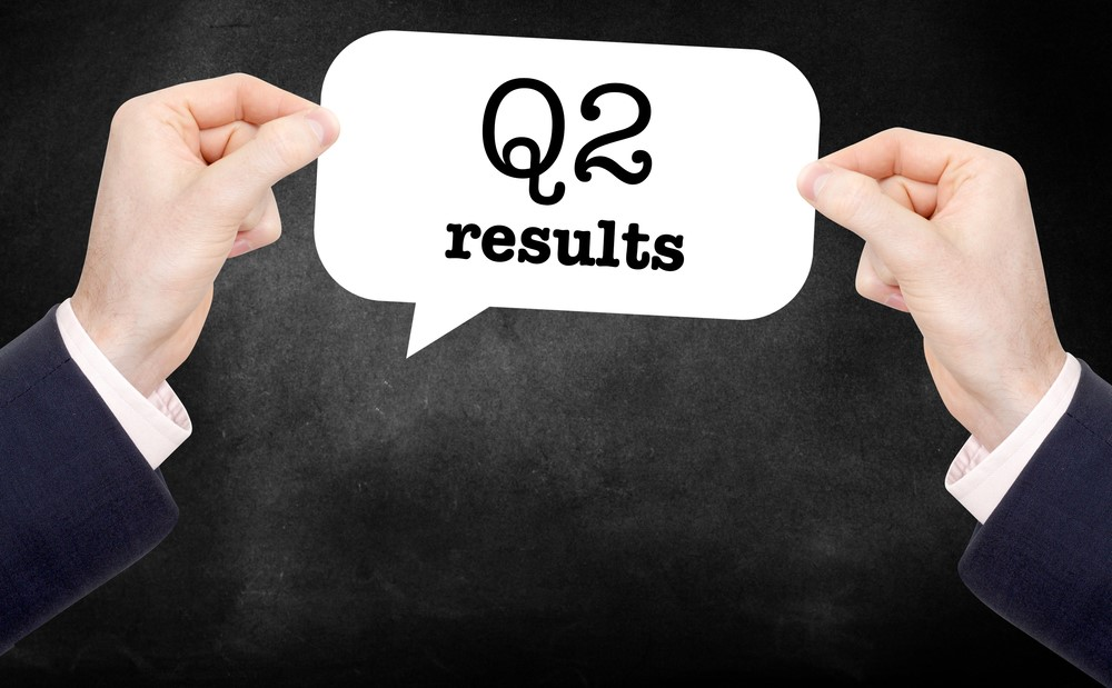 pair-of-hands-holding-paper-which-reads-q2-results