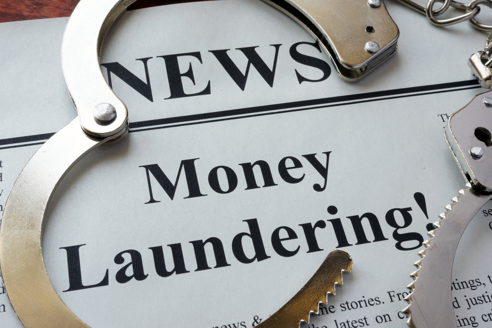 handcuffs on top of newspaper with money laundering headline