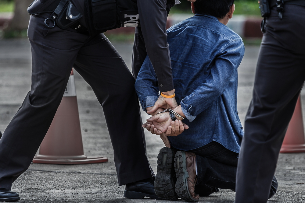 an individual being handcuffed by a police officer