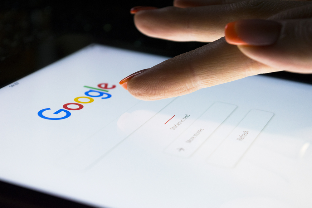 female hands typing into google search on a tablet