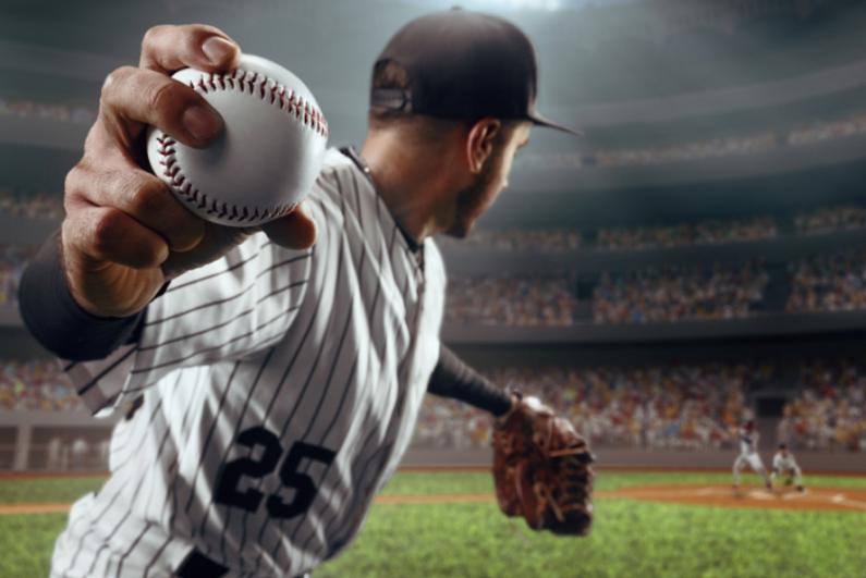 Baseball pitcher throws the ball in professional baseball stadium.