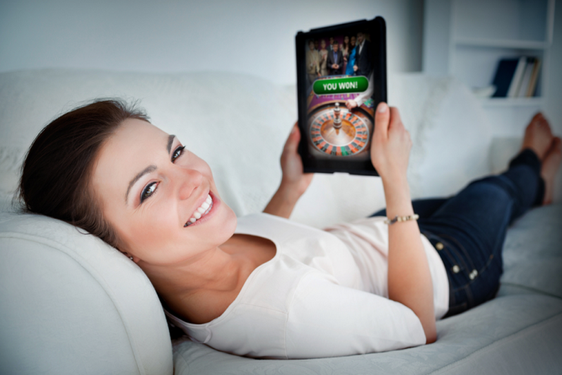 female-gambler-on-couch-using-tablet