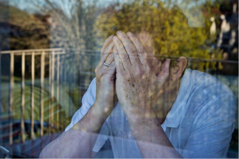 Despondent man with head in hands