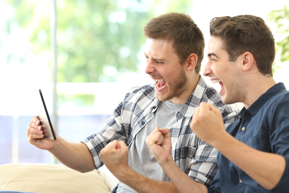 two friends watch mobile screen in excitement