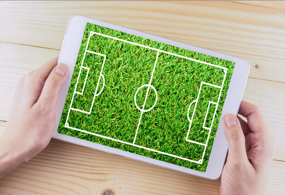 hands holding tablet showing football field image