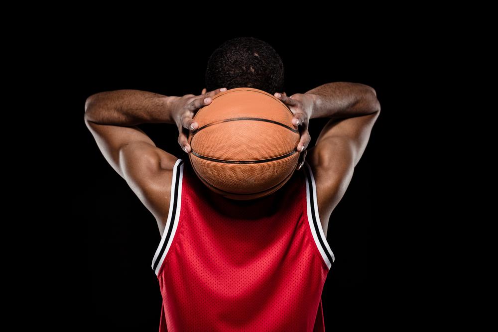 black-man-holding-basketball-behind-his-head