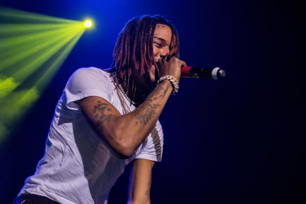 rapper Fetty Wap holding wireless microphone on lit stage