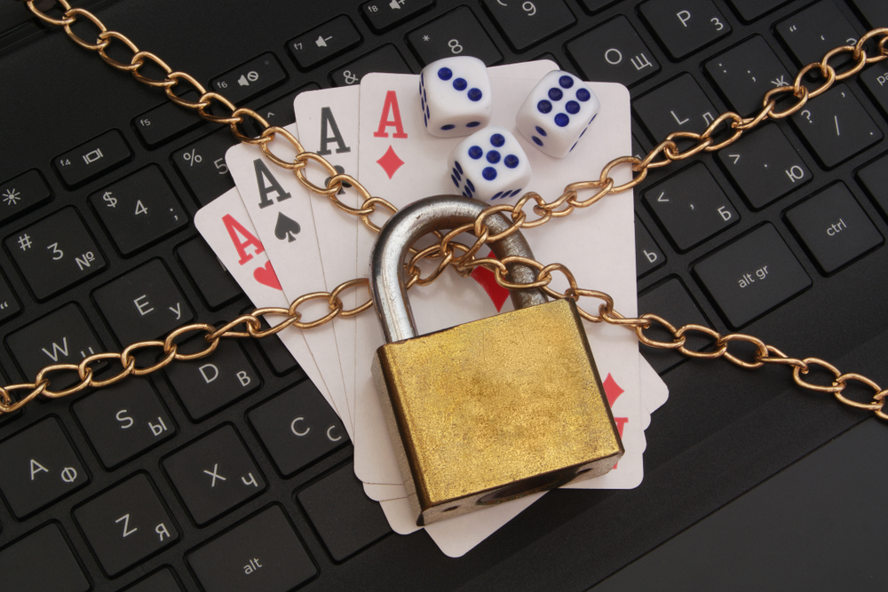 playing cards and dice lying on laptop keyboard held by lock and chains