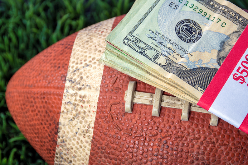 Stack of cash on top of a football.