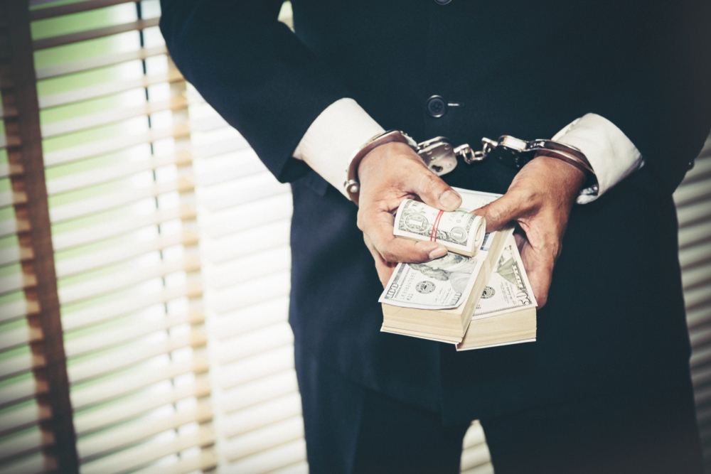 man in suit handcuffed and holding dollar notes