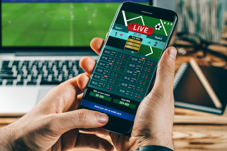 Male making bets using gambling mobile application on his phone while watching sport on laptop.