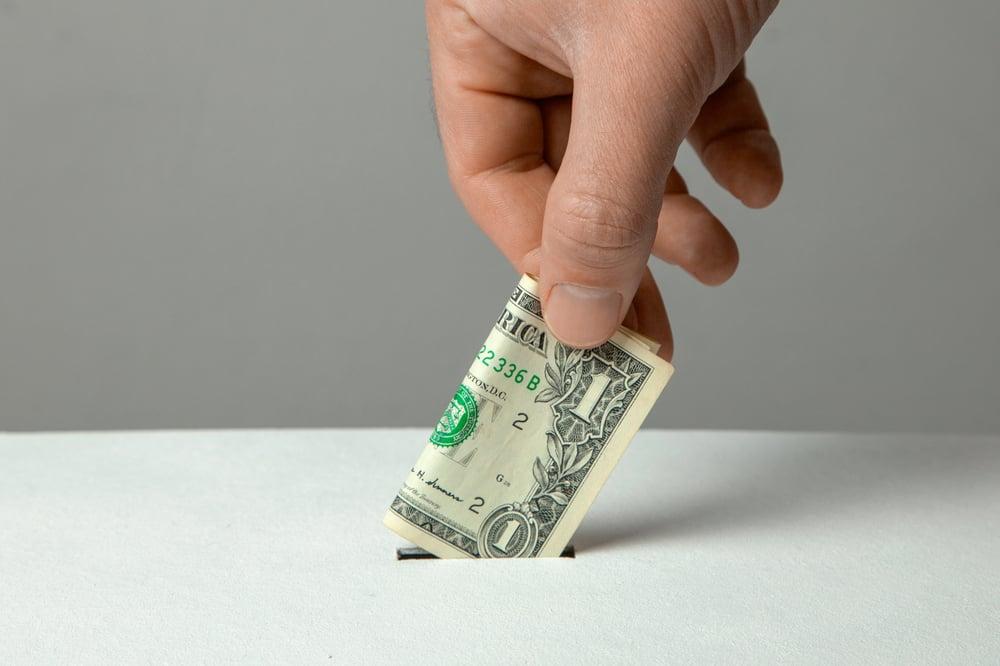 man's hand putting money into donation box slot