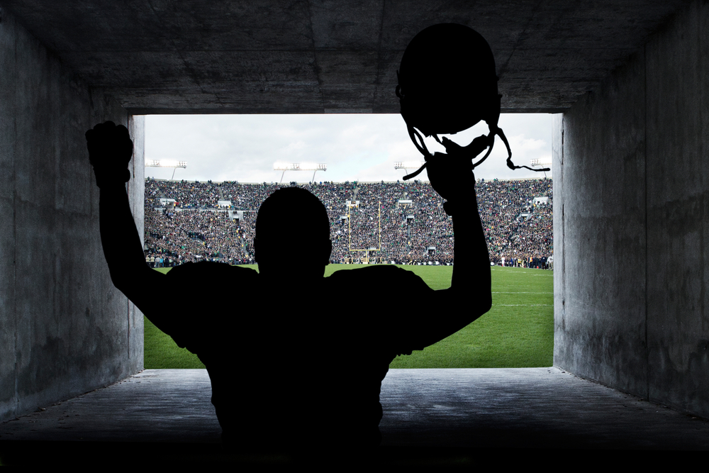 football player holds helmet with arms raised as he's about to enter the football pitch
