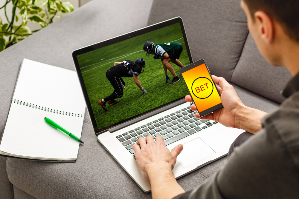 man betting on football using mobile and laptop