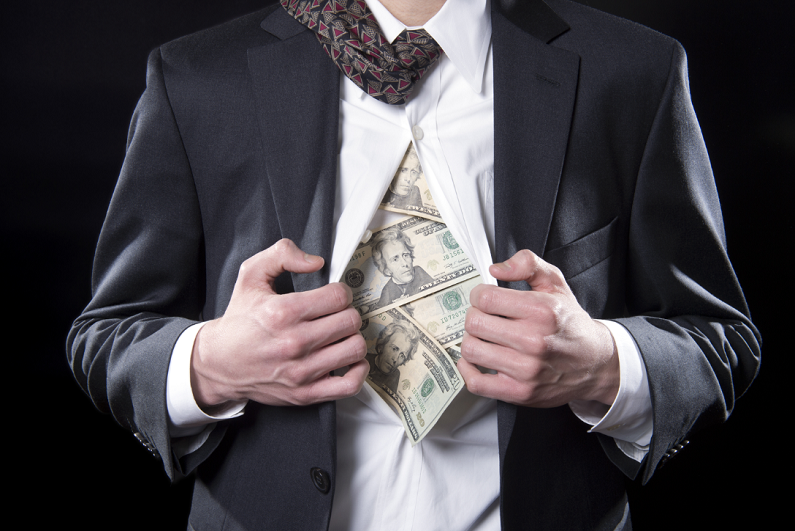 Businessman pulling back his shirt to reveal hidden money.