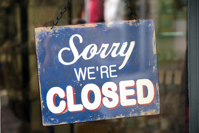 """Vintage """"Sorry, We're Closed"""" sign in a store window."""