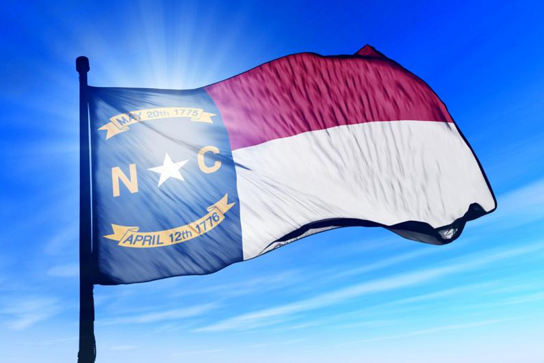 North Carolina flag waving against a blue sky.