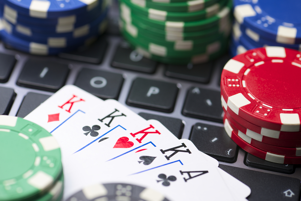 poker chips and cards on a laptop keyboard