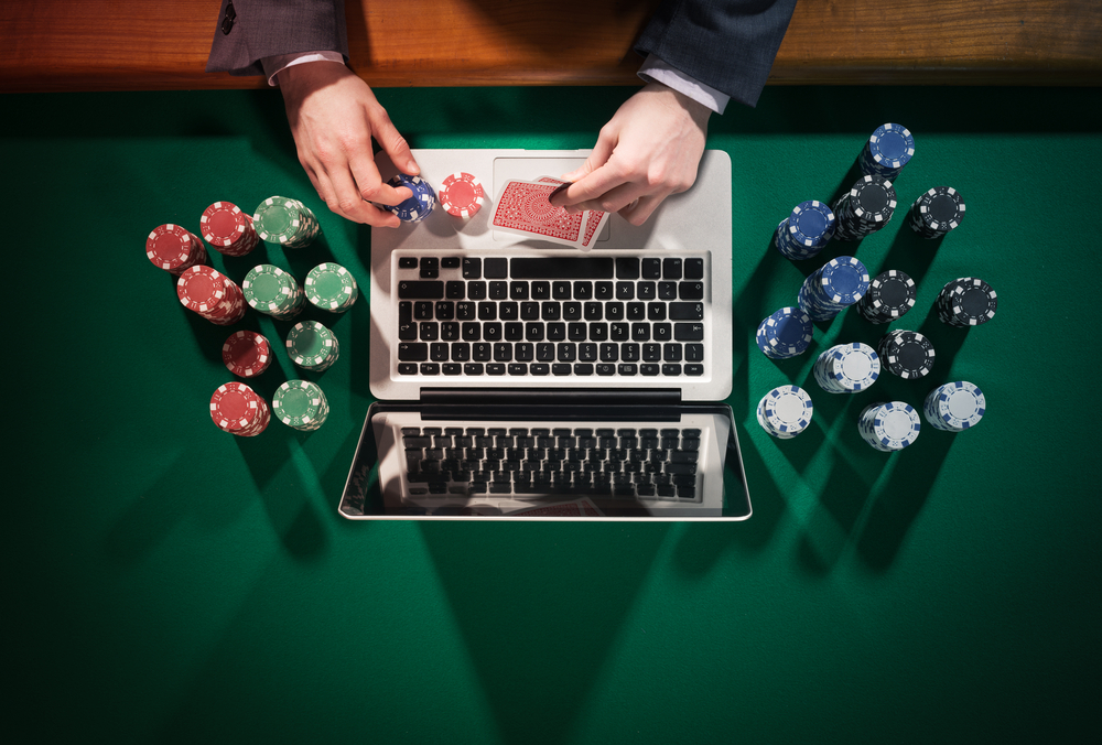 man playing online poker on laptop with poker chips scattered around