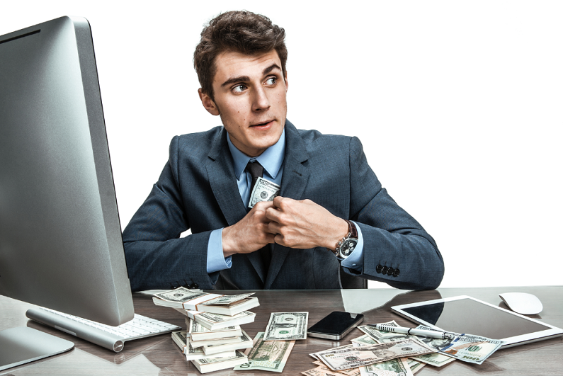 Suited man sitting at a desk and stealing money.