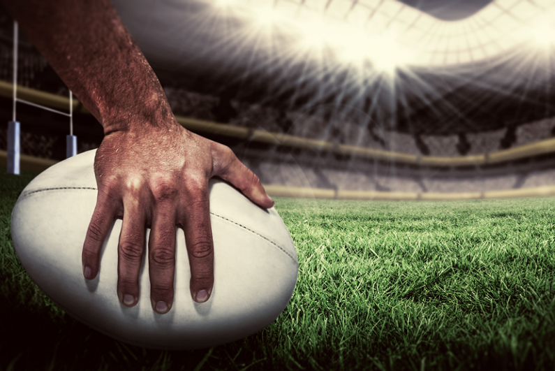 Closeup of a rugby player placing a ball down on the pitch.