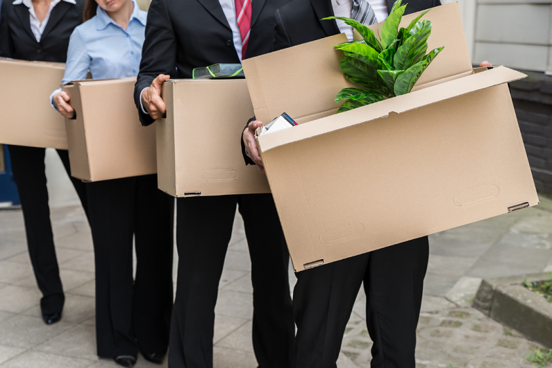 Line of office workers holding boxes of personal items.