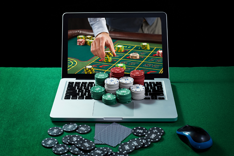 Green table with casino chips and cards on notebook.