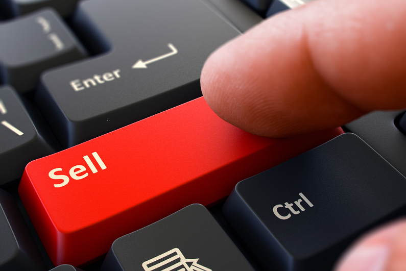 Finger pressing red 'Sell' button on a black keyboard.