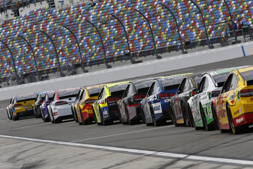 NASCAR cars on a racetrack with audience watching on