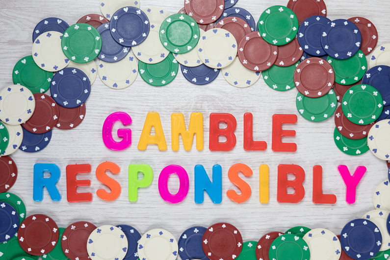 Game responsibly message surrounded by poker chips.