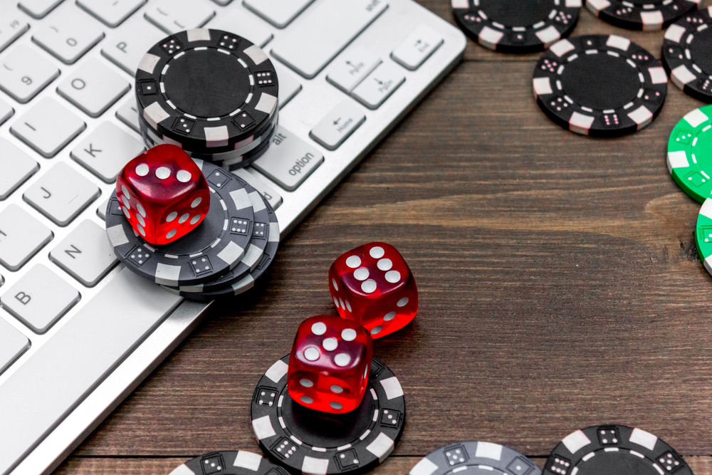 poker chips and dice on a laptop keyoboard