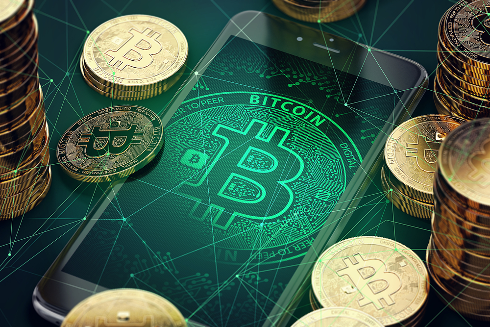 bitcoins scattered around mobile phone displaying the bitcoin symbol