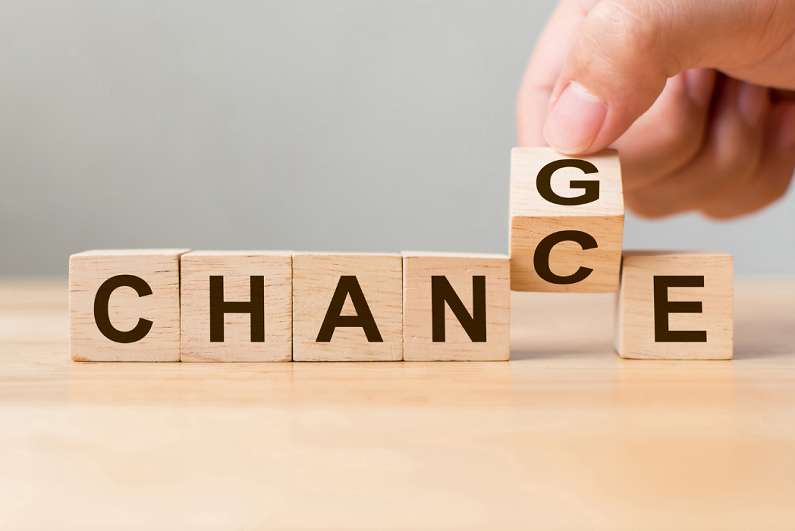 Hand flip wooden cube with word change to chance.