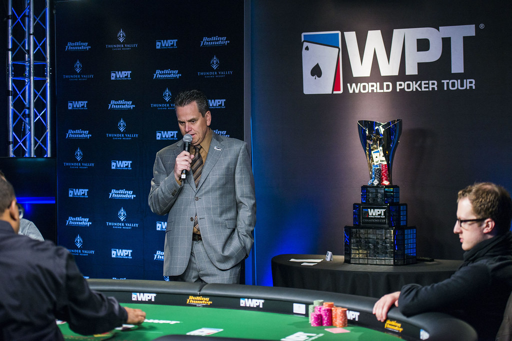 man in suit delivering a speech at a poker tournament