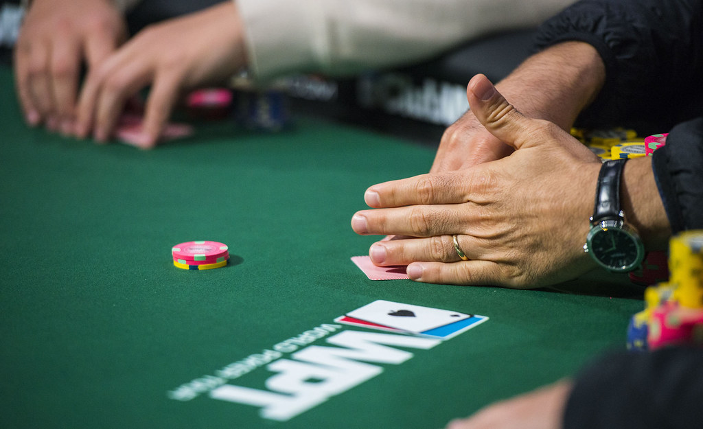 poker players' hands with chips on table with WPT logo