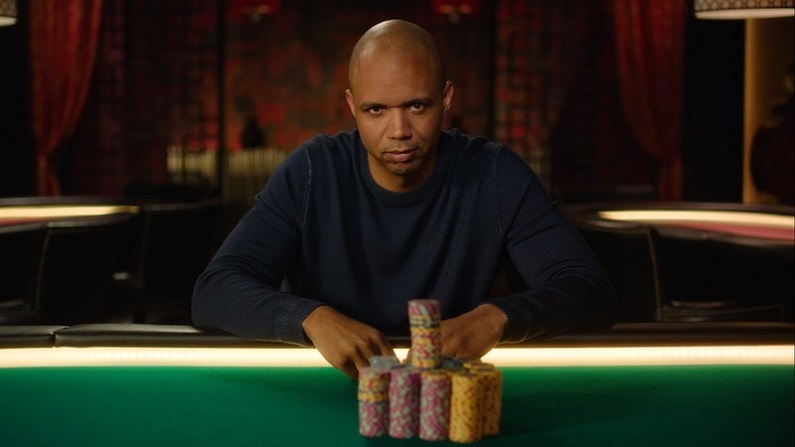 Phil Ivey sitting at poker table with stacks of chips.