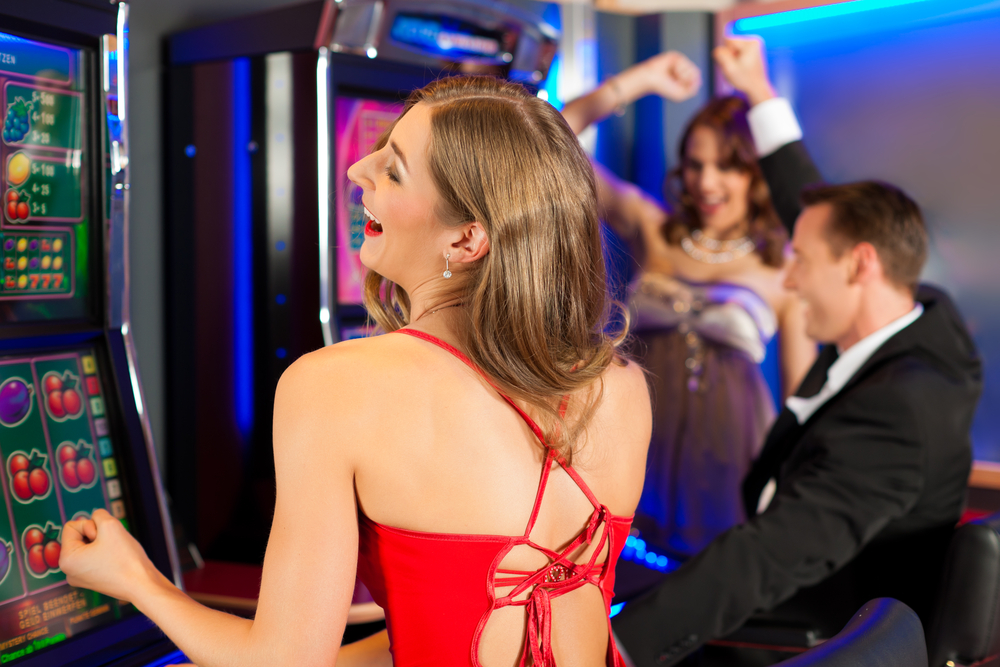 two woman and a man winning at slot machines