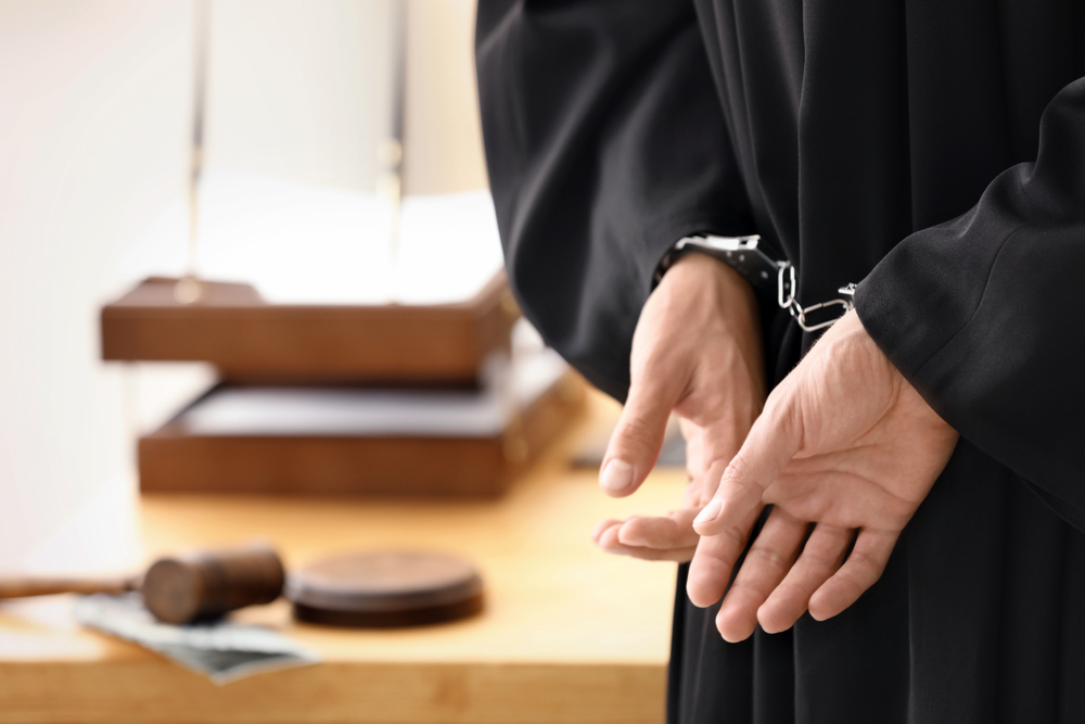man handcuffed in court