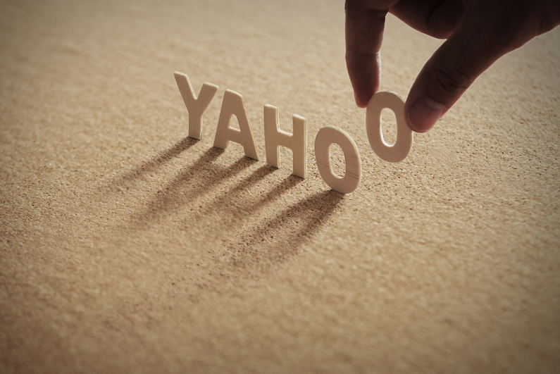 Person lifting letter 'O' from word 'YAHOO' made from wood