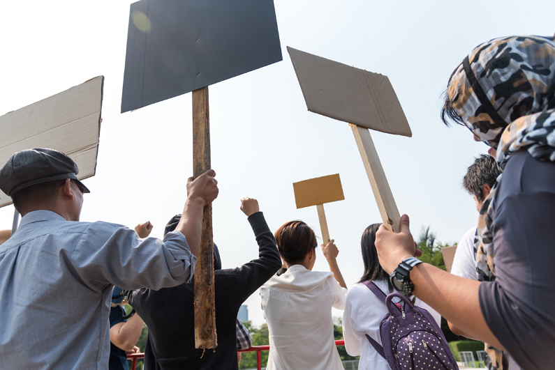Men and women share a protest sign hold a megaphone.