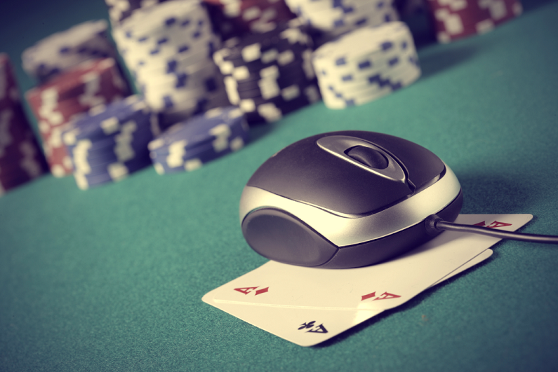 computer mouse sitting on top of playing cards with poker chips in background