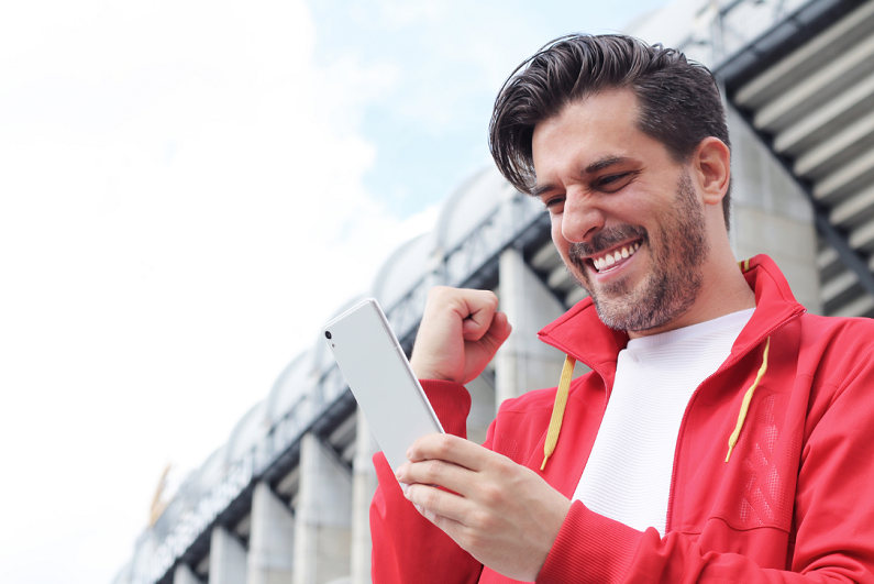 man celebrating winning a bet as he looks at his smartphone