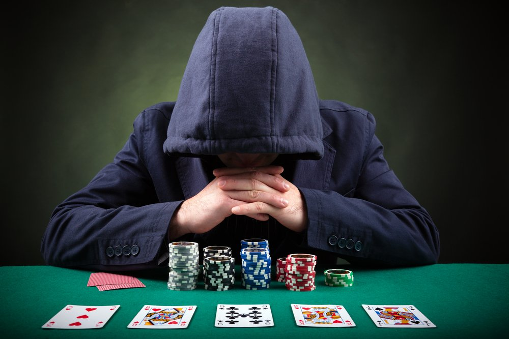 hooded poker player sitting at poker table with cards and chips