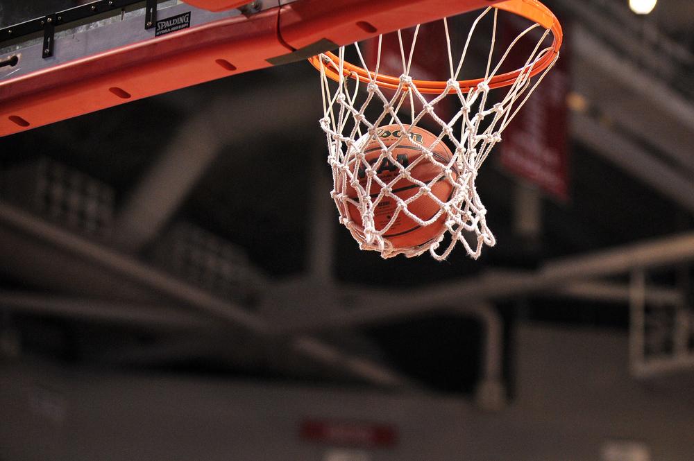 basketball going through hoop in an indoor court