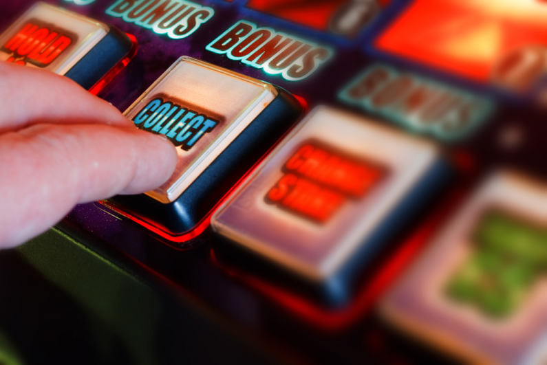 gambler pressing button on a fruit machine