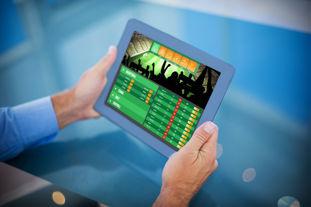 man's hands holding up tablet showing sports betting app